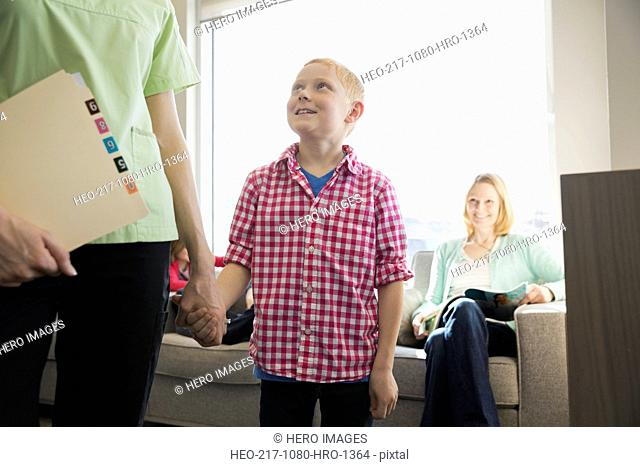 Dental assistant holding hands with boy in lobby