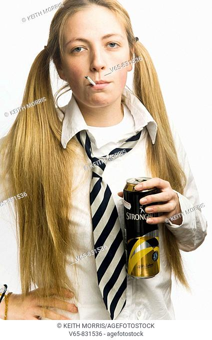 Teenage schoolgirl wearing school uniform smoking cigarette and drinking a can of cider