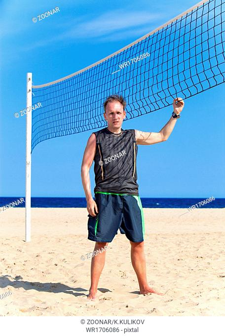 sporting man near a grid for beach volleyball