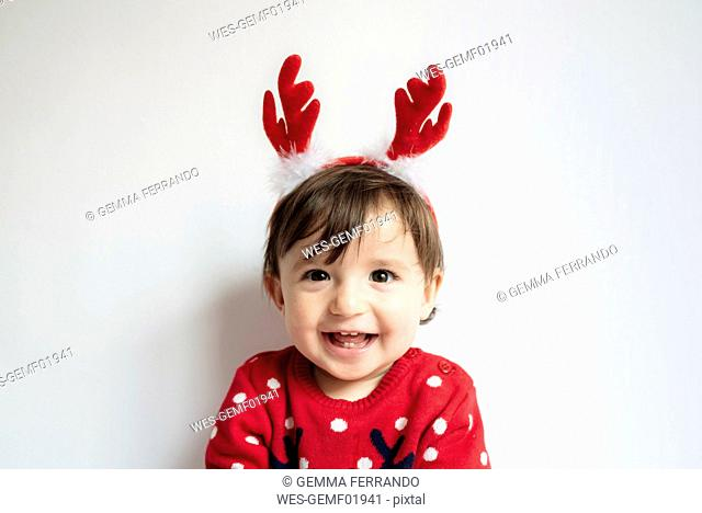 Portrait of laughing baby girl wearing reindeer antlers headband