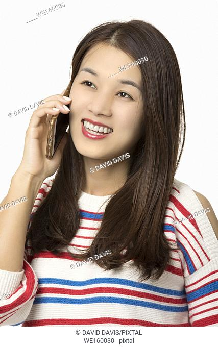 Happyl Asian woman talking on a smartphone isolated on a white background