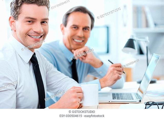 Business partners at work. Side view of two cheerful business people in formalwear smiling at camera while sitting at working place
