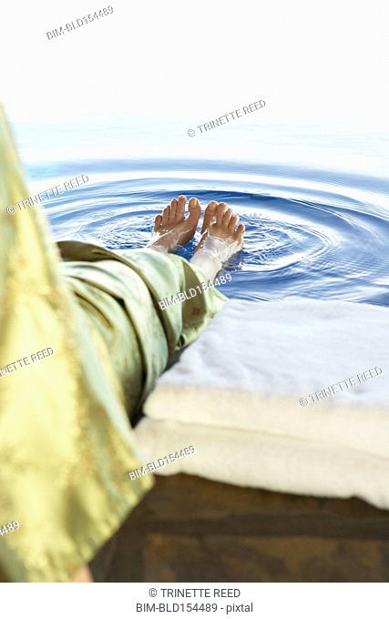 Close up of woman dipping feet in swimming pool