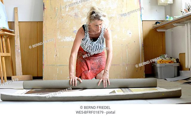 Female painter in her atelier, roll up painting