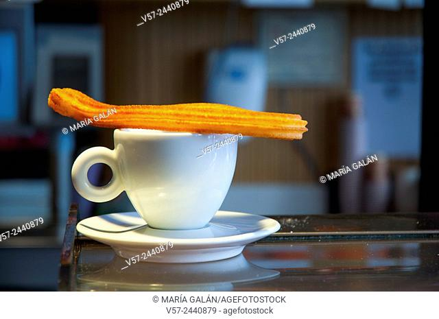 Cup of coffee with a churro on it