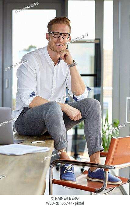 Portrait of smiling businessman with laptop sitting on desk in office