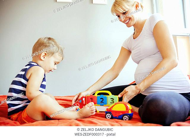 Pregnant mother and son playing on bed