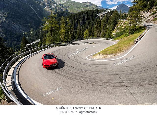 Red convertible travelling on the Maloja Pass, serpentines, winding road, near Sondrio, Lombardy, Italy