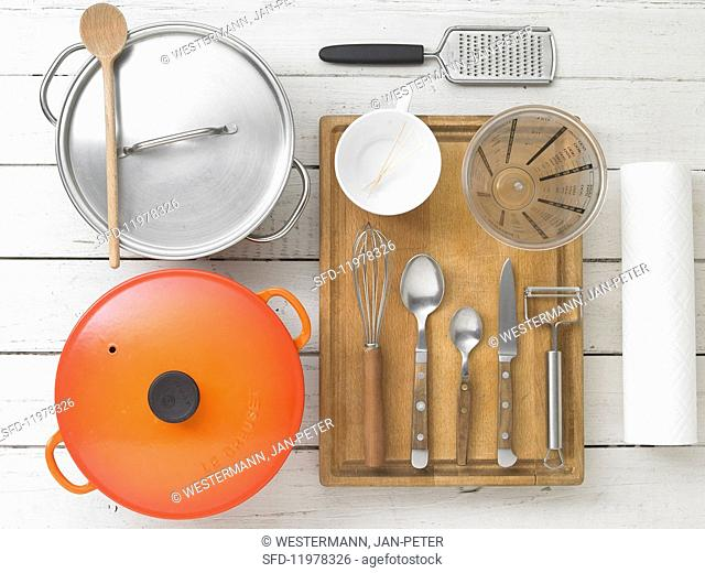 Kitchen utensils: pots, cutlery, a measuring jug, a grater and kitchen paper