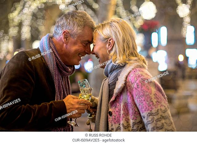Mature couple making a champagne toast on tree lined avenue at xmas, Majorca, Spain