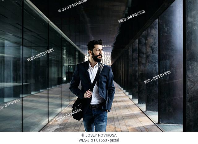 Businessman walking along arcade