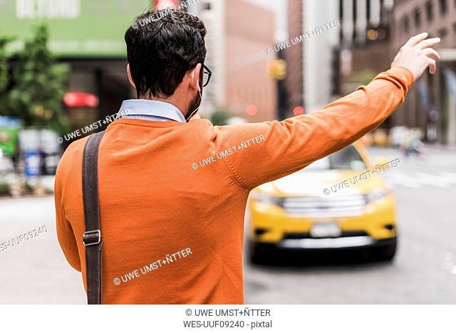 USA, New York City, Businessman hailing cab