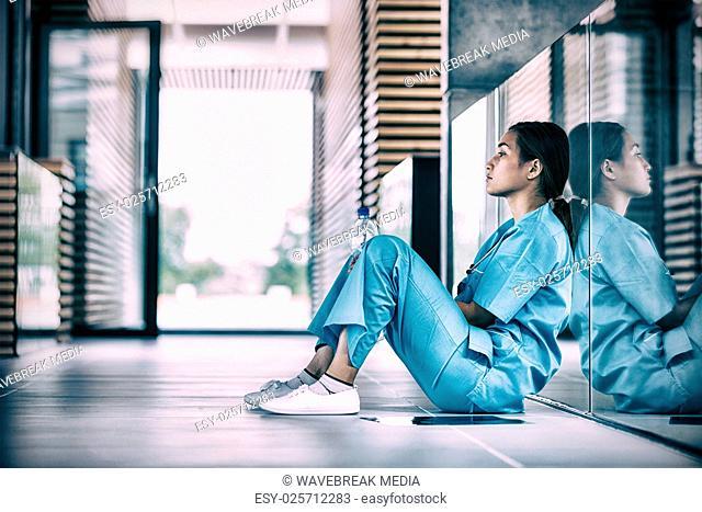 Side view of nurse sitting on floor