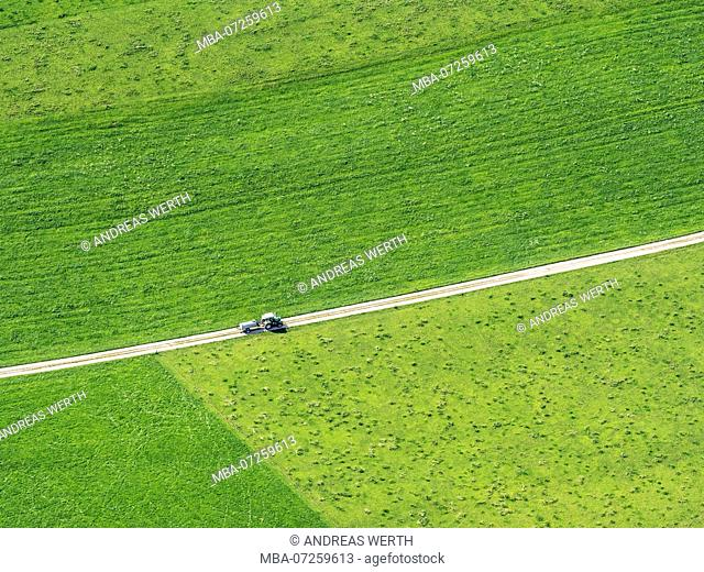 Farm tractor on rural road surrounded by meadows and fields, aerial view, Allgäu, Allgaeu, Bavaria, Germany