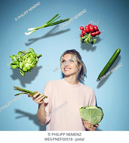 Portrait of happy young woman juggling with vegetables