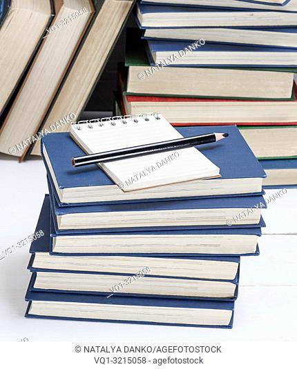 empty notebook with white sheets and a black pencil are on a stack of books