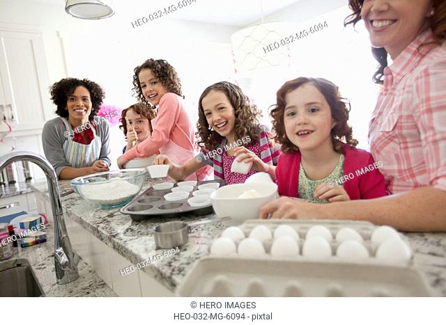 moms and daughters baking in the kitchen