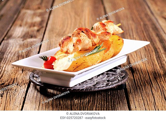 Chicken skewer on slices of roasted potato