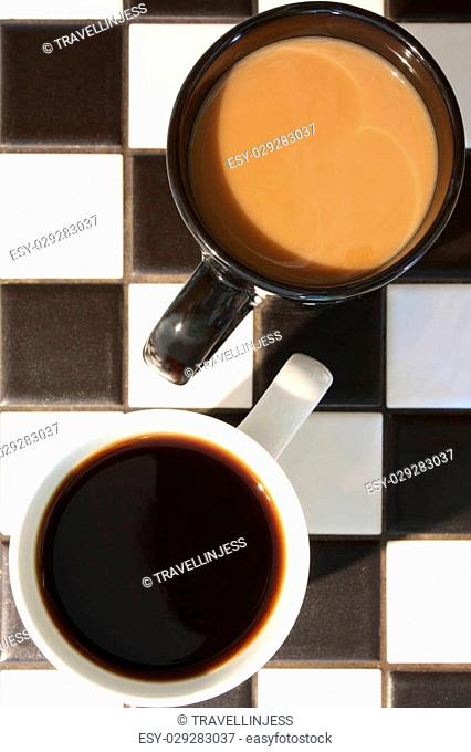 Two cups of coffee, one white (no cream), one black (with cream), on a black and white tile countertop. Possible concept shot for difference or contrast