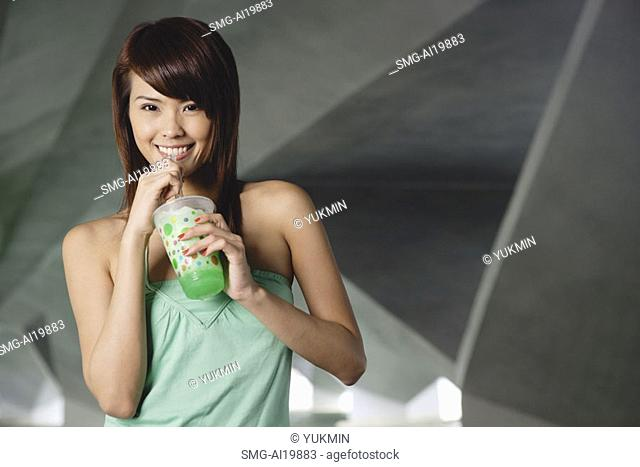 Woman in green top with green drink