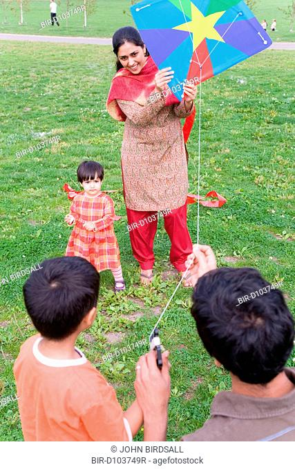 Young family in the park flying a kite