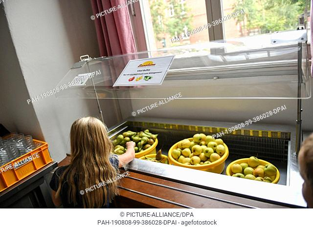 07 August 2019, Berlin: A schoolgirl takes fruit provided for lunch in the canteen of the primary school at Wuhlheide. Photo: Jens Kalaene/dpa-Zentralbild/ZB