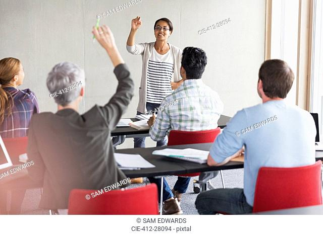 Teacher calling on student with hand raised in adult education classroom