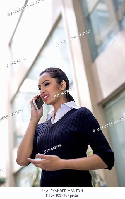 India, Businesswoman talking on mobile phone outside office building