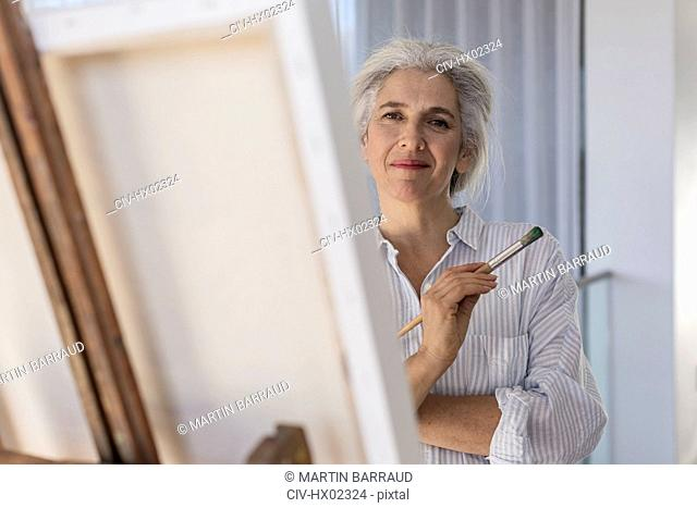Portrait confident mature woman painting at canvas on easel