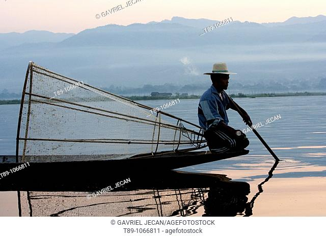 An Intha fisherman with traditional fish trap uses an unusual leg-rowing technique to propel his flat-bottomed boat across the lake while standing
