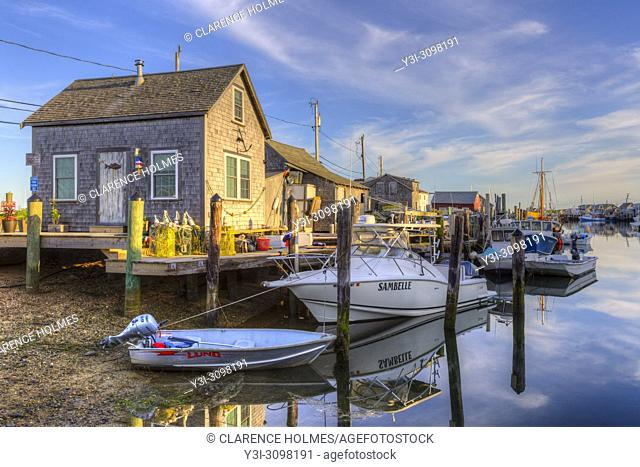 The commercial fishing village of Menemsha and boats docked in Menemsha Basin lit by golden light during the first hour after sunrise, in Chilmark