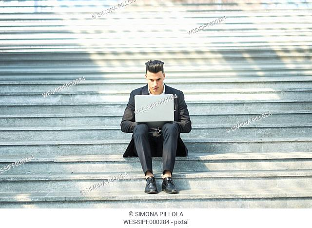 Portrait of businessman sitting on stairs using laptop
