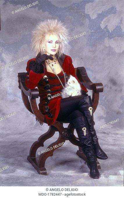 Italian singer-songwriter Ivana Spagna posing sitting on a Savonarola chair with a cat on her lap. Italy, 1988