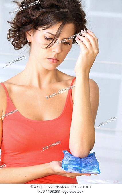 woman cooling her arm with cold bag