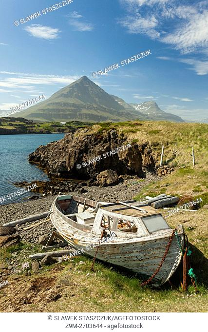 A boat wreck on the shore of a fjord in Iceland