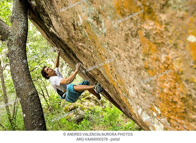 Male Climber Gets Ready To Latch The Next Hold On An Orange Granite Boulder
