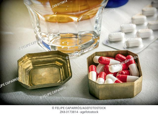 Old pillbox with capsules red and white next to a glass of water