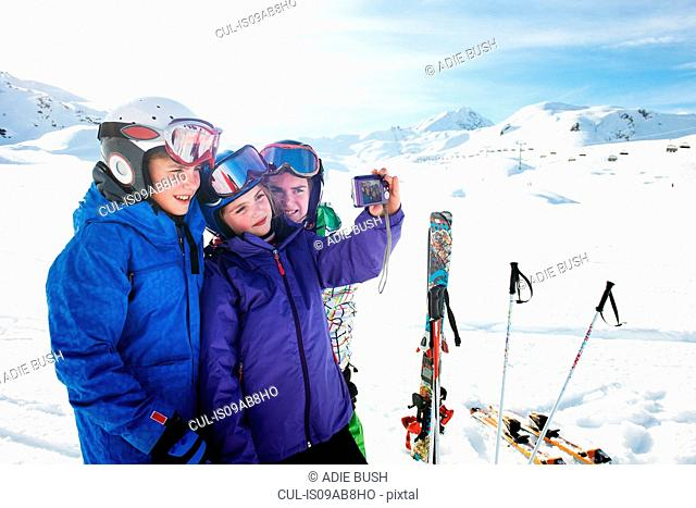 Brother and sisters taking self portrait, Les Arcs, Haute-Savoie, France