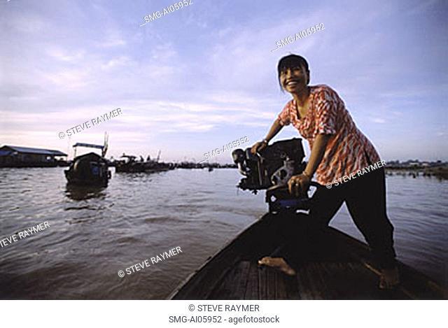 Vietnam, Long Xuyen, Woman driving boat in floating markets on Mekong River