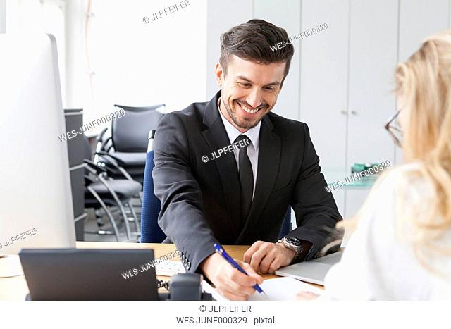 Portrait of smiling businessman with customer in an office