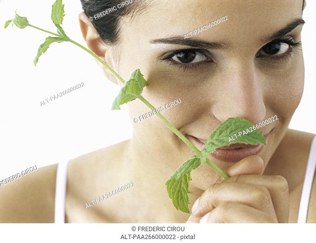 Woman holding sprig of mint to nose, smiling at camera, close-up