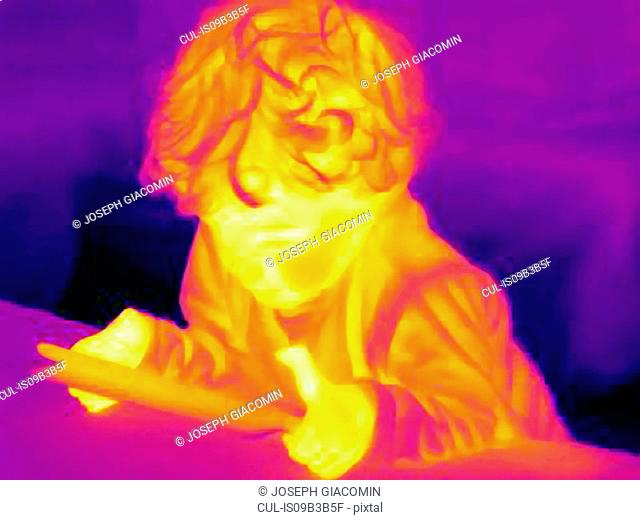 Thermal image of male toddler using digital tablet