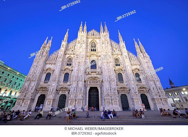 Tourists in front of the west facade of Milan Cathedral or Duomo di Santa Maria Nascente, in the evening light, Milan, Lombardy, Italy