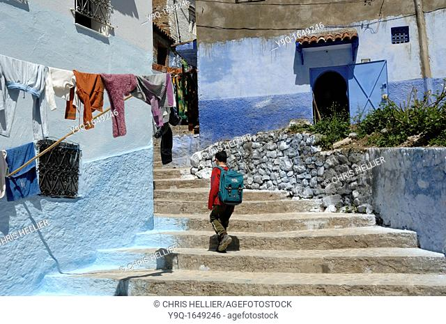 A Moroccan Boy Climbs Steps at Chefchaouen Morocco