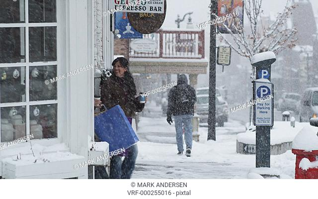 two women walking out of a shop onto a snowy street