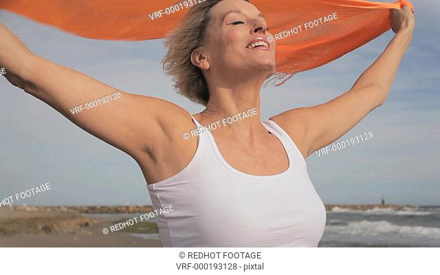 Woman standing on windy beach with orange scarf