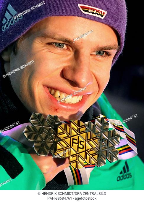Andreas Wellinger from Germany holds up his silver medal he won at the men's large hill jumping event on the previous day during the Medal Ceremony at the...
