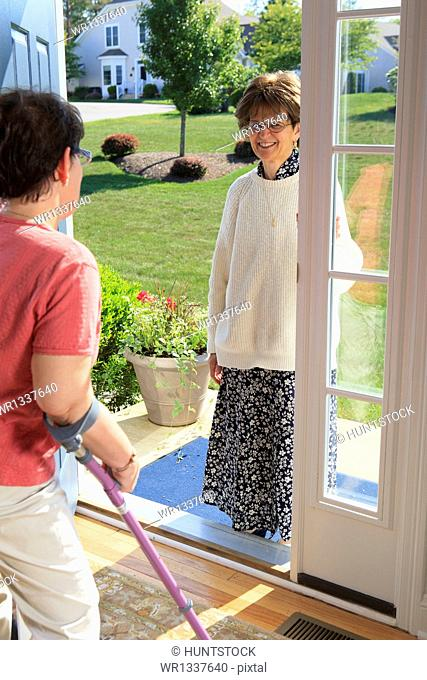 Woman with cerebral palsy greeting someone at the door of her home