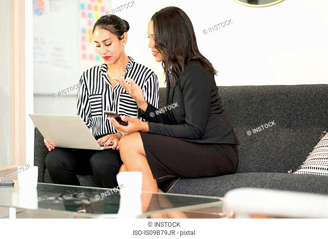 Two businesswomen sitting on office sofa, using laptop, looking at screen