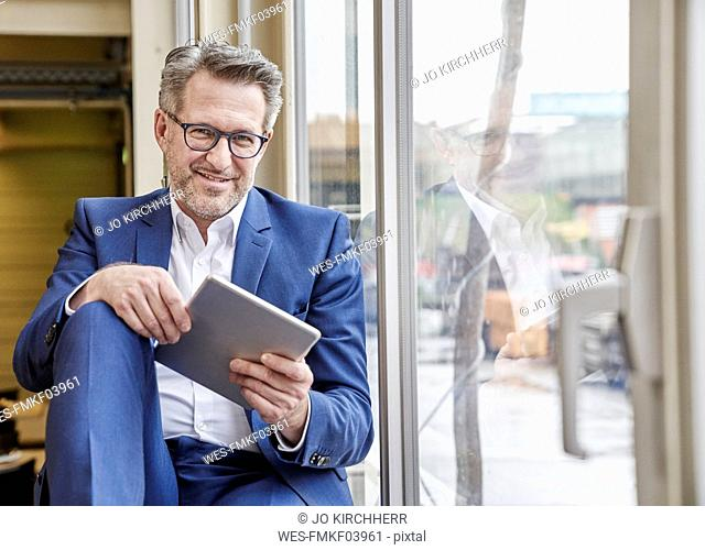 Smiling mature businessman using tablet at the window